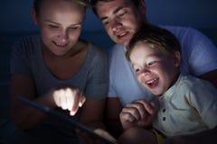 Родители и сын с ПК таблетки внешним поздно в Стоковые Фото