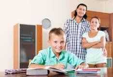 Родители наблюдая, как их сын сделал домашнюю работу Стоковое Фото