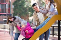 Родители наблюдая маленький отбрасывать дочерей Стоковое Фото