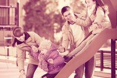 Родители наблюдая маленький отбрасывать дочерей Стоковые Фото