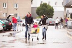 Родители нажимая магазинную тележкау с бакалеями и их дочерьми Стоковые Изображения