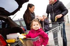 Родители нажимая магазинную тележкау с бакалеями и их дочерьми Стоковые Фотографии RF