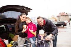 Родители нажимая магазинную тележкау с бакалеями и их дочерьми Стоковые Фото