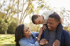 Родители нося сына на плечах по мере того как они идут в парк Стоковое Изображение