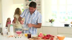 Родители подготавливая завтрак семьи в кухне видеоматериал