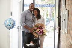 Родители приезжая домой с Newborn младенцем в автокресло Стоковые Фотографии RF