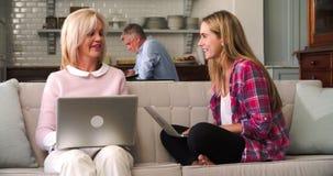 Родители при взрослая дочь используя портативные компьютеры дома сток-видео