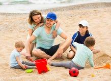 Родители при дети играя в песке Стоковые Изображения RF