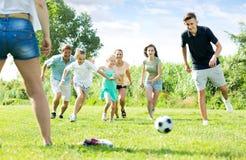 Родители при дети играя футбол на внешнем Стоковое фото RF