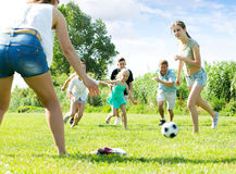 Родители при дети играя футбол на внешнем Стоковые Изображения