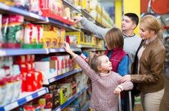 Родители при 2 дет выбирая гроуты в продовольственном магазине Стоковое фото RF