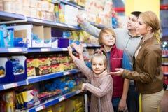 Родители при 2 дет выбирая кудрявые хлопья в магазине Стоковые Фотографии RF