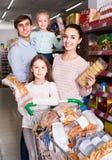 Родители при 2 дет выбирая печенья в магазине Стоковое Изображение