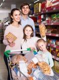 Родители при 2 дет выбирая печенья в магазине Стоковая Фотография RF