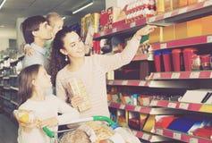 Родители при 2 дет выбирая печенья в магазине Стоковые Фото
