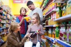 Родители при 2 дет выбирая соду Стоковое фото RF