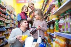 Родители при 2 дет выбирая соду Стоковые Изображения