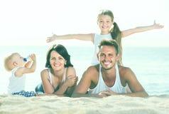 Родители при 2 дет лежа на пляже Стоковые Фотографии RF