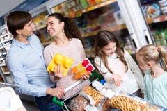 Родители при 2 дет покупая югурт плодоовощ Стоковое Фото