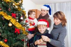 Родители при 2 дет украшая рождественскую елку Стоковое Фото