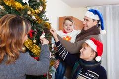 Родители при 2 дет украшая рождественскую елку Стоковые Фото