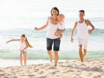 Родители при 2 дет jogging на пляже Стоковые Изображения RF