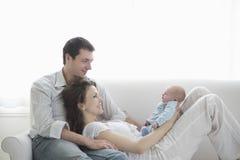 Родители при младенец ослабляя на софе стоковое изображение