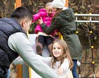 Родители при 2 дочери играя на скольжении детей Стоковая Фотография