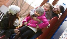 Родители при 2 дочери играя на скольжении детей Стоковое Изображение RF