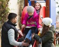 Родители при 2 дочери играя на скольжении детей Стоковое Фото