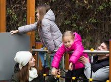 Родители при 2 дочери играя на скольжении детей Стоковая Фотография RF