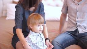 Родители при ребенок сидя на кровати акции видеоматериалы