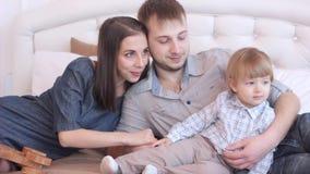 Родители при ребенок сидя на кровати видеоматериал