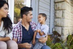 Родители при сын сидя на шагах вне дома Стоковое фото RF