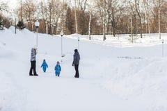 Родители с близнецами сыновьей идут в парк зимы на солнечный день Стоковые Изображения