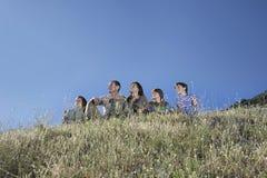 Родители с 3 детьми на холме против голубого неба Стоковая Фотография