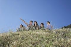 Родители с 3 детьми на холме против голубого неба Стоковое фото RF