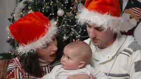 Родители целуют щеки маленького младенца, рождества видеоматериал
