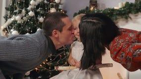 Родители целуют щеки маленькой девочки, рождества акции видеоматериалы