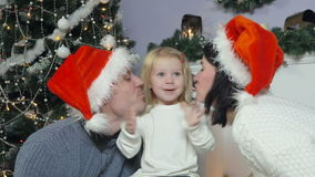 Родители целуют щеки маленькой девочки, рождества видеоматериал