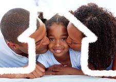 Родители целуя их дочь против плана дома в предпосылке Стоковое Фото