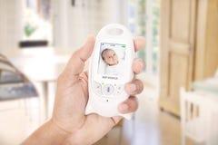 Родительский младенец контроля через монитор младенца Стоковые Изображения