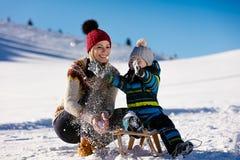 Родительство, мода, сезон и концепция людей - счастливая семья при ребенок на скелетоне идя в зиму outdoors стоковые изображения rf