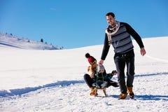 Родительство, мода, сезон и концепция людей - счастливая семья при ребенок на скелетоне идя в зиму outdoors стоковое фото