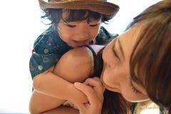 Родитель и сын hagging усмехаться в полдень Стоковое фото RF