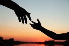 Родитель силуэта держит руку achild Стоковые Изображения RF