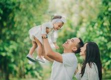 Родитель с их милым младенцем в парке имея потеху совместно стоковые изображения