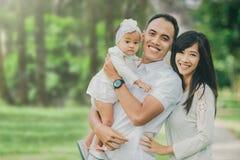 Родитель с их милым младенцем в парке имея потеху совместно стоковые фото