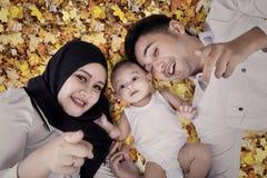 2 родителя и их сын лежа на листьях осени Стоковое Изображение RF