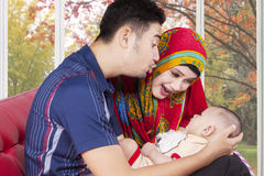 2 родителя ослабляя на софе с младенцем Стоковые Фото